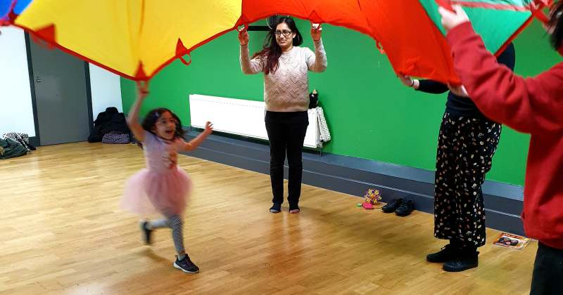 Three adults lift a large multicoloured parachute in the air while a small dark-haired girl in a pink dress runs underneath.