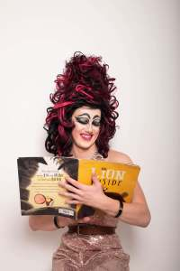 "Aida H Dee, a drag queen with a red and black neon wig and dramatic eye makeup, smiles as she reads from a picture book entitled ""The Lion Inside""."