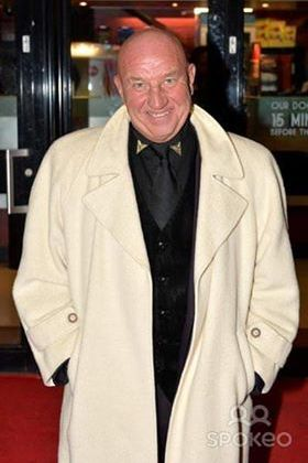 Dave Courtney, a bald white man, grins at the camera from a red carpet event.